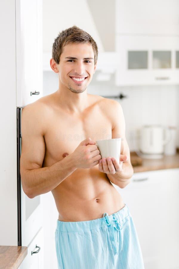 Homem semi-nua com o copo do chá na cozinha imagens de stock