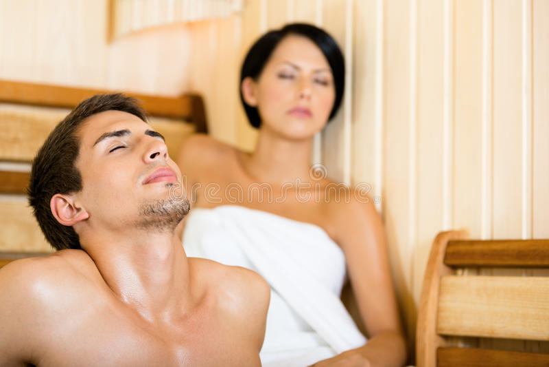 Homem semi-nua e menina que relaxam na sauna foto de stock