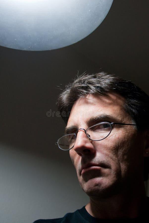 Homem severo sob a luz fotos de stock royalty free