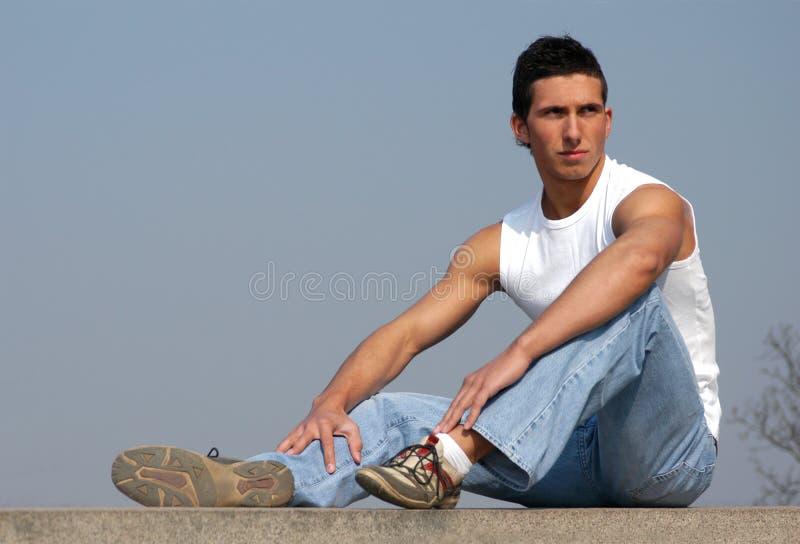 Homem 'sexy' de assento com céu azul atrás fotos de stock royalty free
