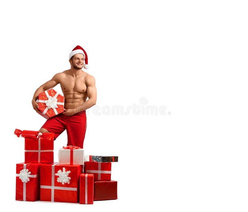 Homem 'sexy' de Santa Claus com uma pilha dos presentes fotos de stock royalty free
