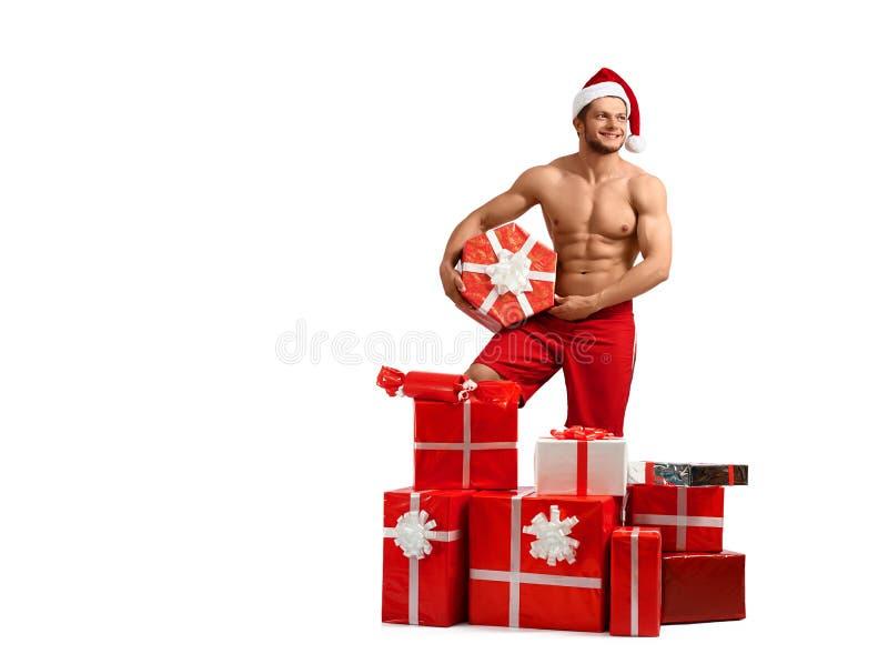 Homem 'sexy' de Santa Claus com uma pilha dos presentes fotografia de stock