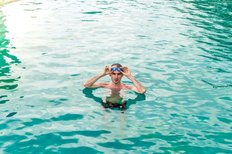 Homem 'sexy' do ajuste com os óculos de proteção que relaxam na piscina imagem de stock royalty free