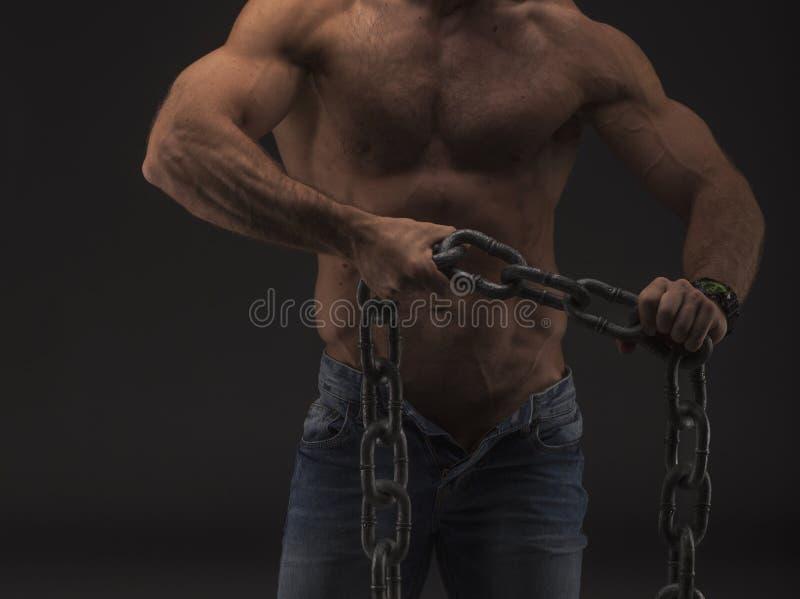 Homem 'sexy' muscular com corrente grande somente nas calças de brim Corpo masculino do nude forte com veias imagem de stock royalty free