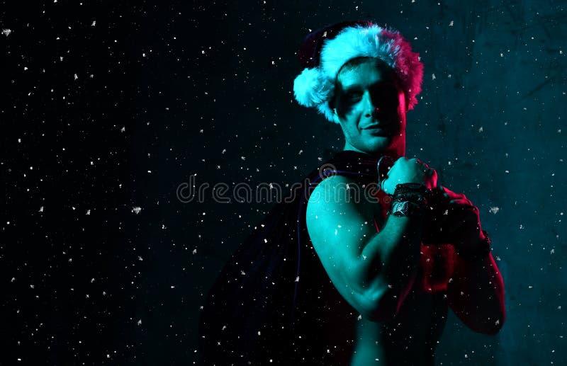 Homem 'sexy' no traje de Santa Claus Christmas com saco completamente dos presentes sob confetes da neve imagens de stock royalty free