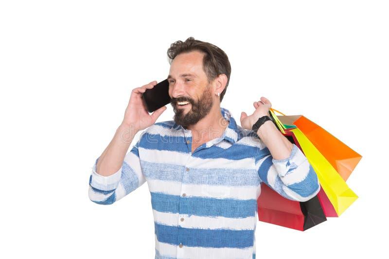 Homem shopaholic satisfeito que compartilha de suas emoções de compra ao falar no telefone celular imagens de stock royalty free