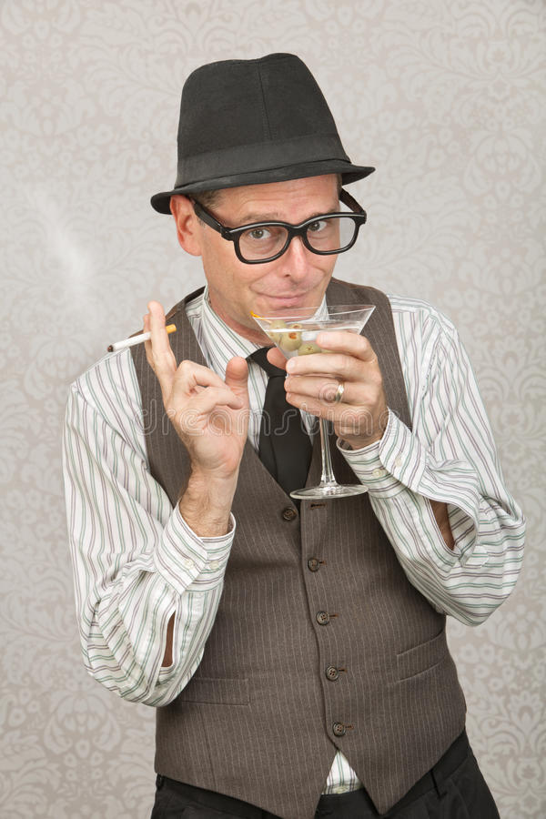 Homem Smirking que sorve Martini imagem de stock