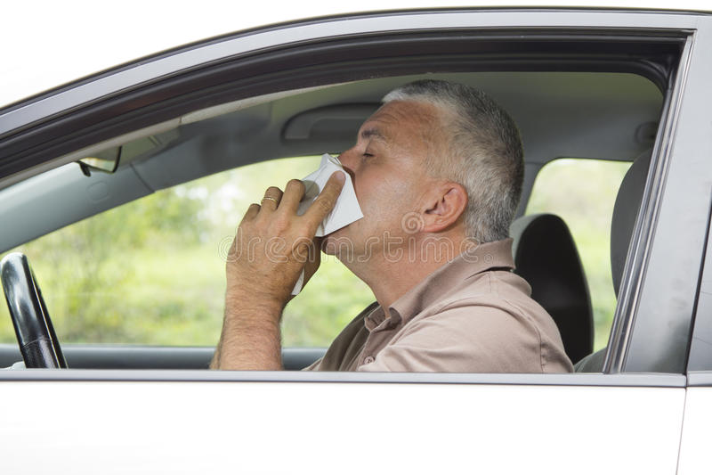 Homem Sneezing no carro fotografia de stock