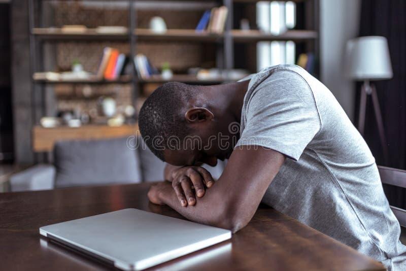 Homem sobrecarregado que dorme perto do portátil fotos de stock