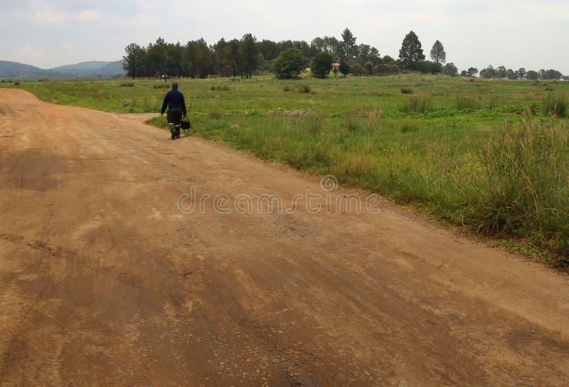 Homem solitário que anda em uma estrada de terra fotografia de stock royalty free