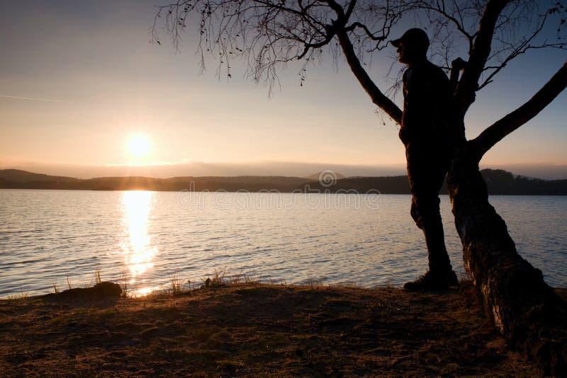 Homem solitário que olha o por do sol colorido na costa do lago do outono Árvore de vidoeiro do fole do suporte do homem imagens de stock royalty free