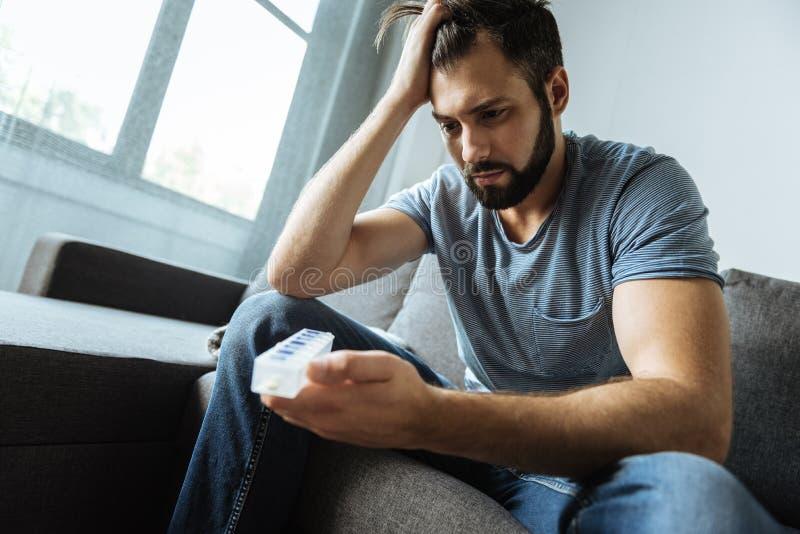 Homem sombrio deprimido que guarda um organizador do comprimido fotos de stock royalty free