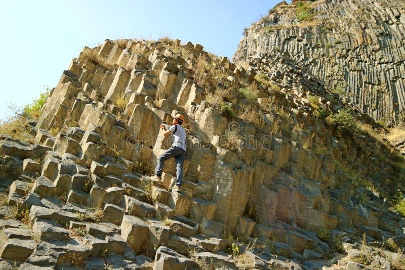 Homem Subindo a Sinfonia das Pedras, Formações Massivas de Coluna Basalt ao longo do desfiladeiro Garni na Armênia imagem de stock