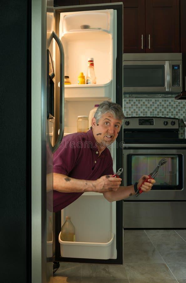 Homem sujo engraçado do proprietário do reparo do dispositivo no refrigerador fotografia de stock royalty free