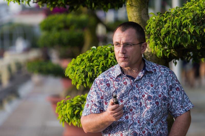 Homem superior adulto que vaping o cigarro eletrônico exterior imagens de stock