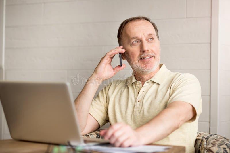 Homem superior agradável que fala no telefone celular fotos de stock royalty free