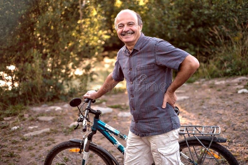 Homem superior alegre que está com uma bicicleta em um parque em um dia ensolarado bonito fotografia de stock