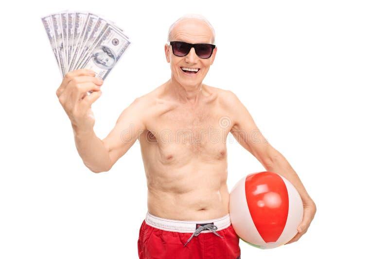 Homem superior alegre que guarda o dinheiro e uma bola de praia fotografia de stock