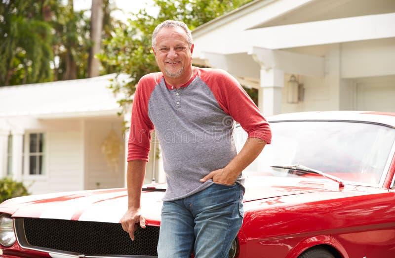 Homem superior aposentado que está ao lado do carro clássico restaurado imagens de stock