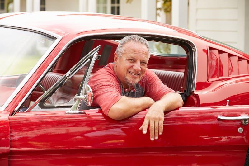 Homem superior aposentado que senta-se no carro clássico restaurado imagens de stock royalty free