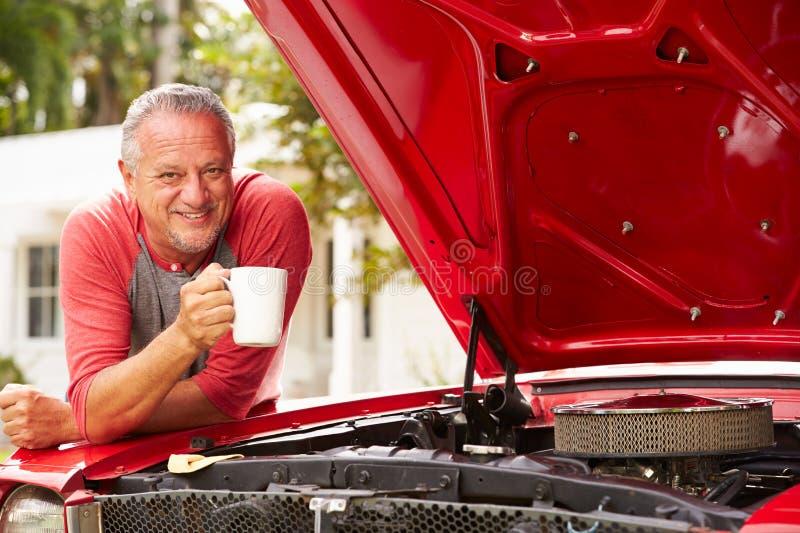 Homem superior aposentado que trabalha no carro clássico restaurado fotos de stock