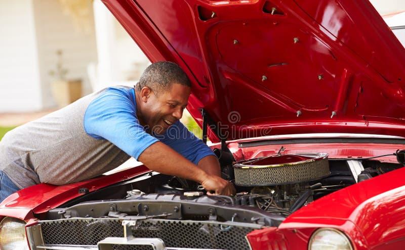Homem superior aposentado que trabalha no carro restaurado fotos de stock royalty free