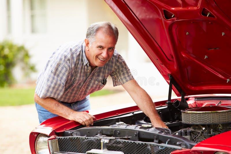 Homem superior aposentado que trabalha no carro restaurado imagens de stock royalty free