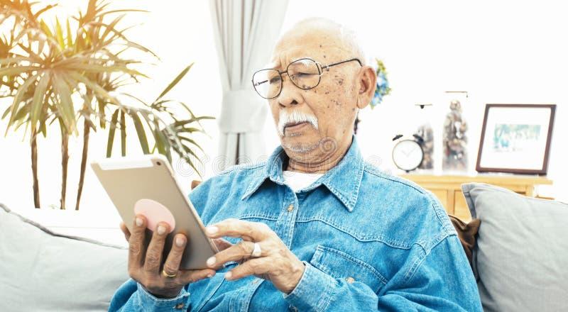 Homem superior asiático com bigode branco usando o tablet pc em casa fotos de stock