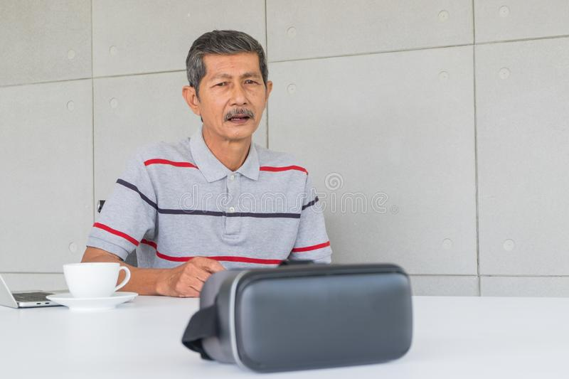 Homem superior asiático com vidros de VR para a tecnologia moderna imagens de stock