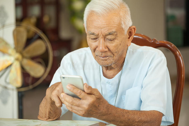 Homem superior asiático feliz que usa o telefone celular imagens de stock