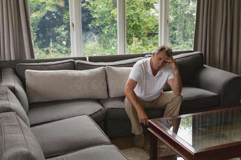Homem superior ativo com mão na testa que senta-se no sofá em uma casa confortável imagens de stock royalty free
