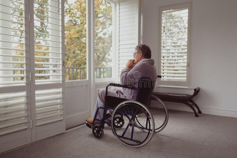 Homem superior ativo deficiente que olha através da janela na cadeira de rodas em uma casa confortável fotografia de stock royalty free