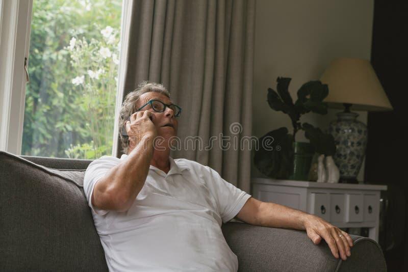 Homem superior ativo que senta-se no sofá e que fala no telefone celular na sala de visitas na casa confortável imagem de stock