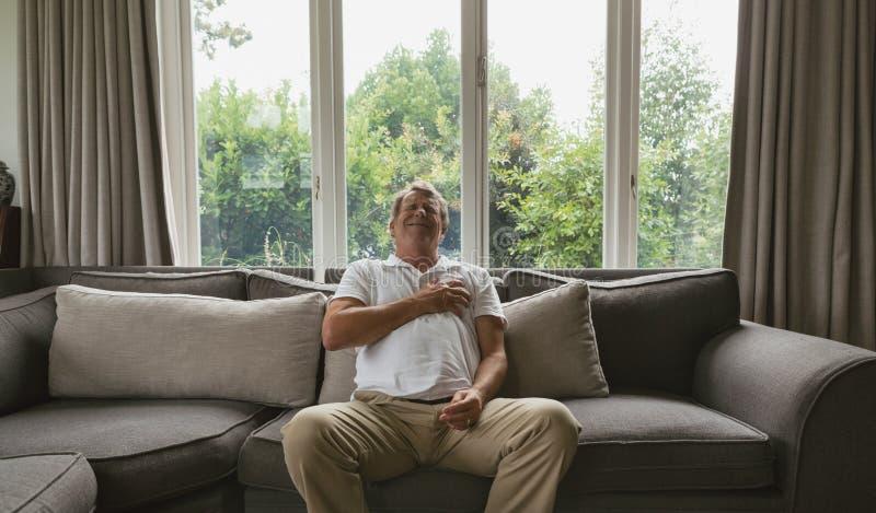 Homem superior ativo que sofre da dor no peito no sofá em uma casa confortável foto de stock royalty free