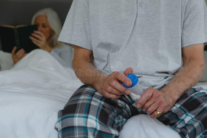 Homem superior ativo que toma a medicina no quarto em casa imagens de stock royalty free