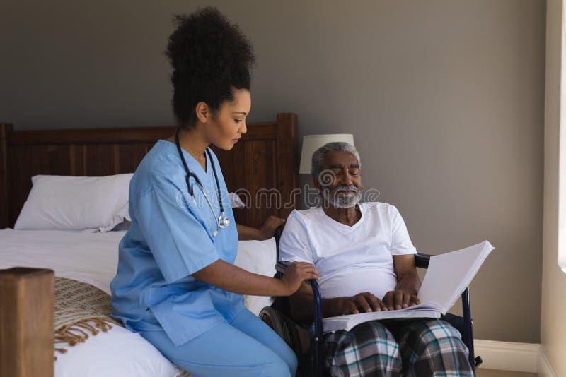 Homem superior cego que lê um braile com doutor fêmea fotografia de stock royalty free