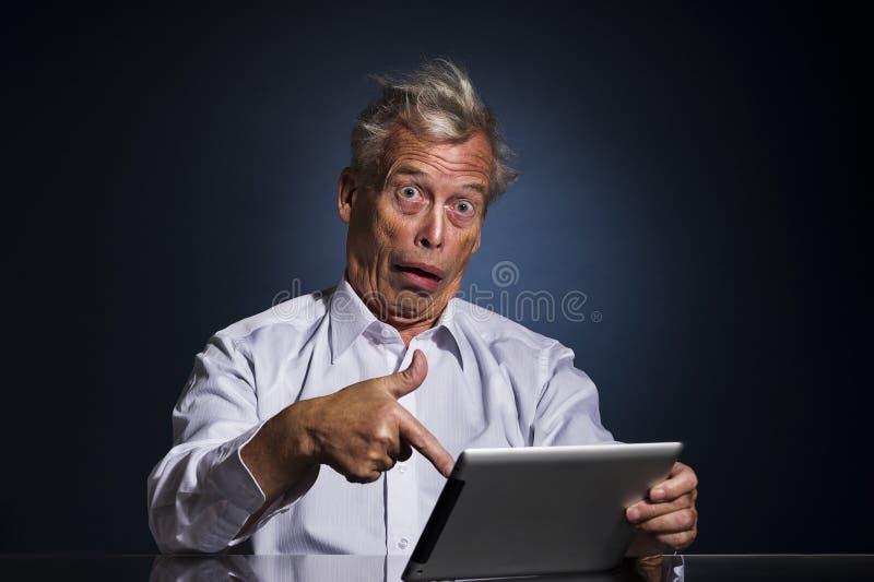 Homem superior chocado que aponta a sua tabuleta foto de stock royalty free