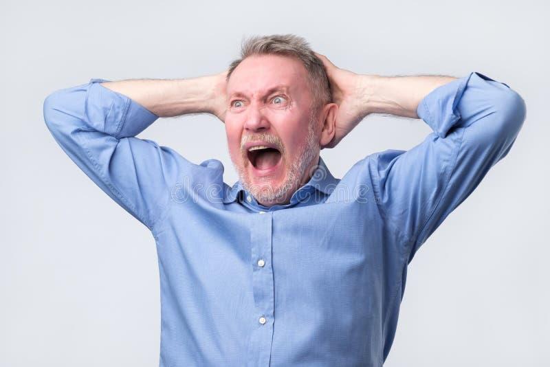 Homem superior com a careta irritada em sua cara, com a boca aberta no grito fotografia de stock royalty free