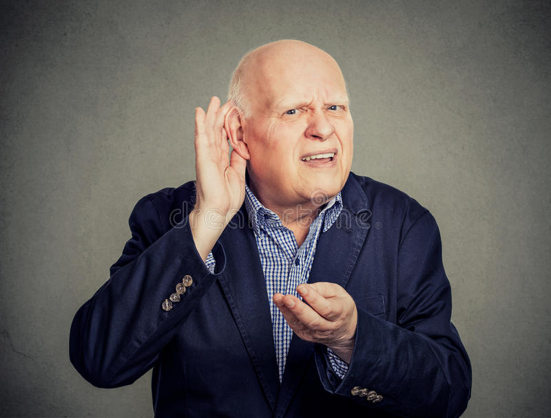 Homem superior, com deficiência auditiva, colocando a mão na orelha pedindo que alguém fale acima foto de stock royalty free