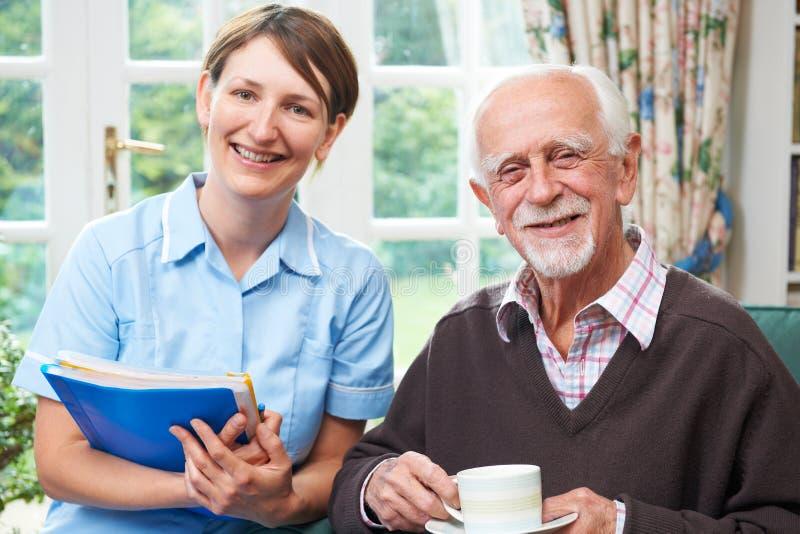 Homem superior com equipa de tratamento em casa imagens de stock royalty free