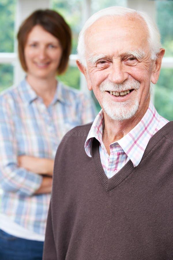 Homem superior com filha adulta em casa fotos de stock