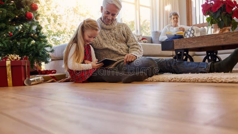 Homem superior com a neta que usa a tabuleta digital em casa imagens de stock royalty free