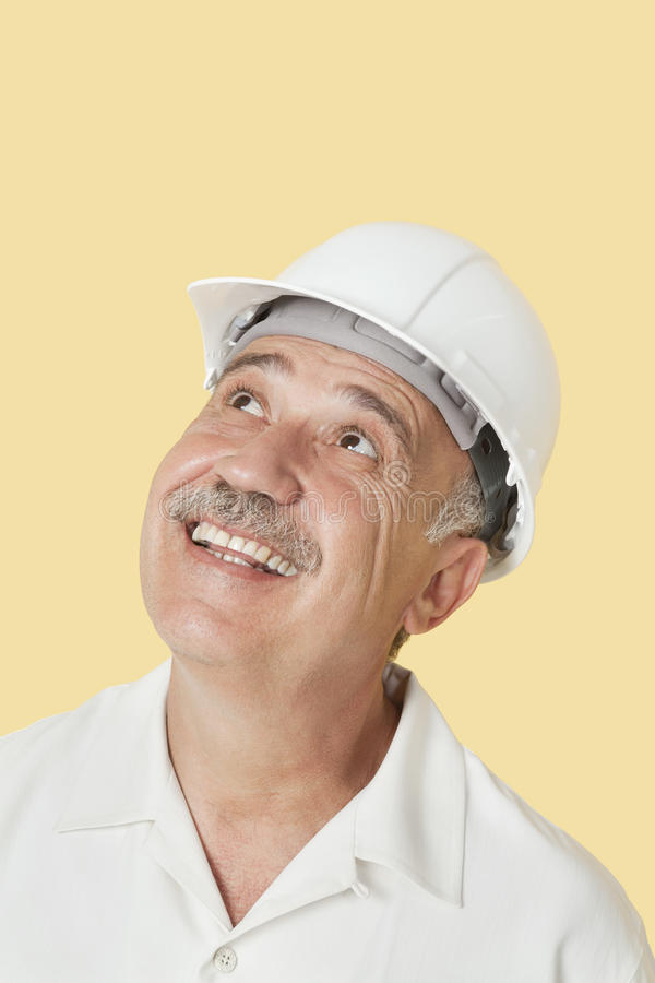 Homem superior com o capacete de segurança que olha acima e que sorri sobre o fundo amarelo fotografia de stock royalty free