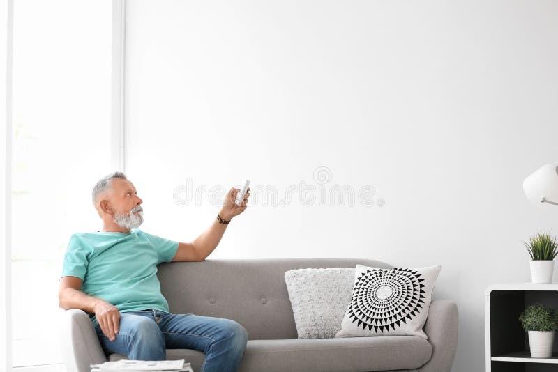 Homem superior com o contro do telecontrole do condicionador de ar imagens de stock