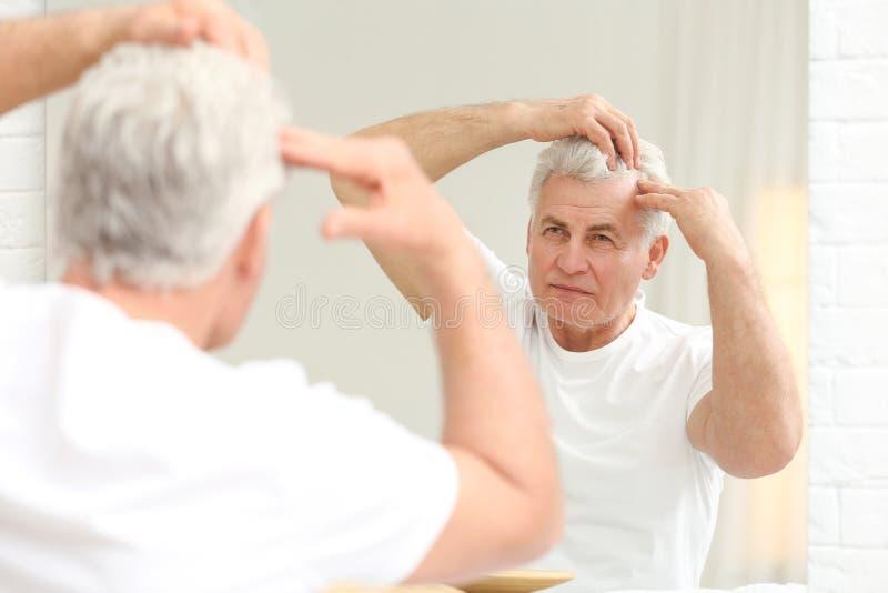Homem superior com o problema da queda de cabelo que olha no espelho fotografia de stock royalty free