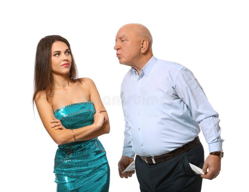 Homem superior com os bolsos vazios que tentam beijar a jovem mulher no fundo branco Uni?o de conveni?ncia fotografia de stock