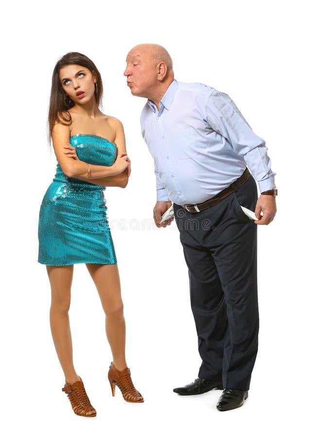 Homem superior com os bolsos vazios que tentam beijar a jovem mulher no fundo branco Uni?o de conveni?ncia imagem de stock royalty free