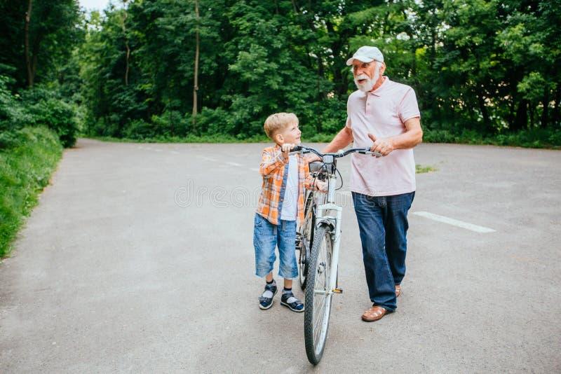 Homem superior com seu passeio pequeno do neto exterior fotografia de stock royalty free