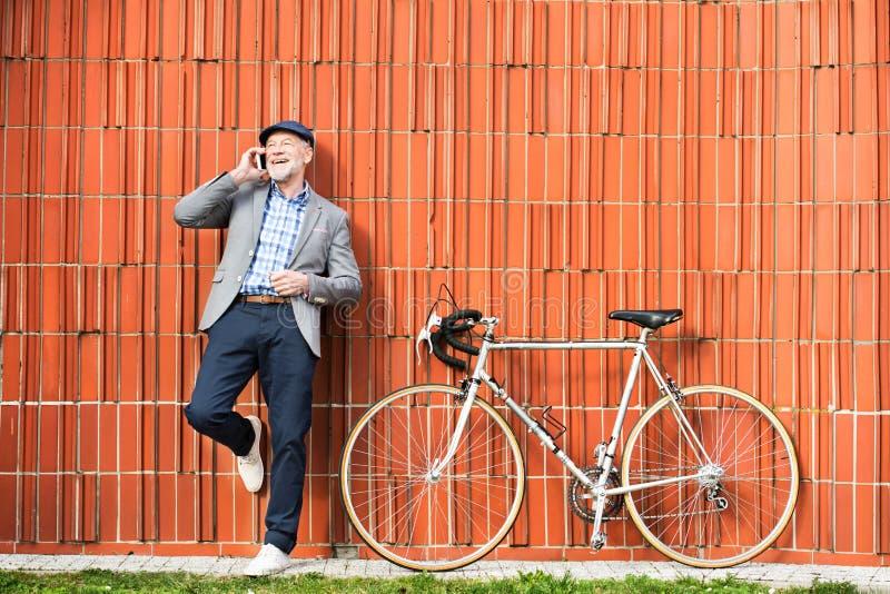 Homem superior com smartphone e bicicleta contra a parede de tijolo fotos de stock royalty free
