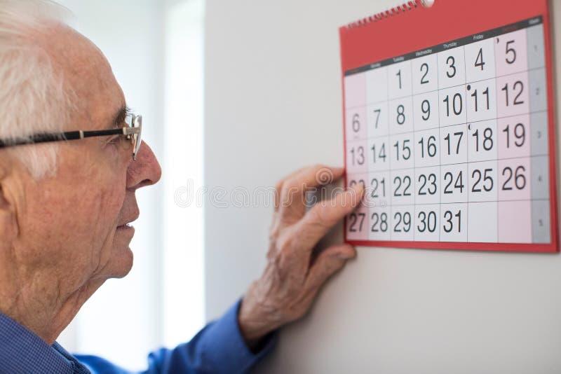 Homem superior confuso com a demência que olha o calendário de parede foto de stock